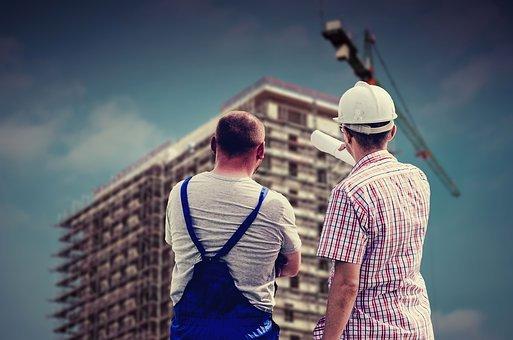 Deux hommes avec un casque regardent un building en construction